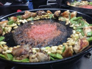 Cooking paella meat and vegetables